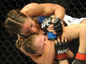 Liz Carmouche grabs hold of Ronda Rousey in the very first female bout inside the UFC octagon.